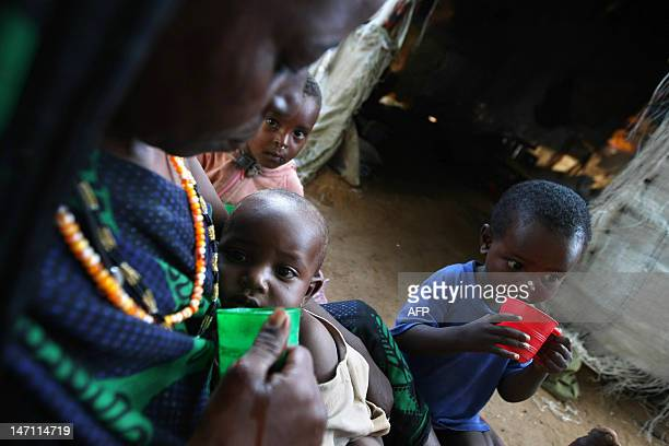A mother feeds her children with porridge for breakfast at an IDP camp 17km outskirts of Mogadishu on May18 2009 Families at different IDP camps are...