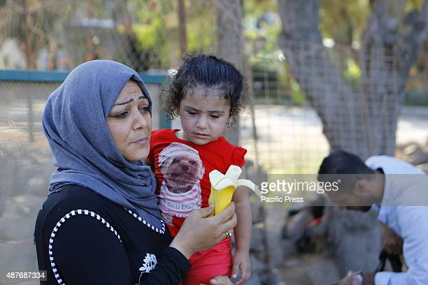 A mother feeds her daughter a banana Hundreds of refugees mainly from Syria Iraq and Afghanistan are still coming to the Greek island of Lesbos on a...
