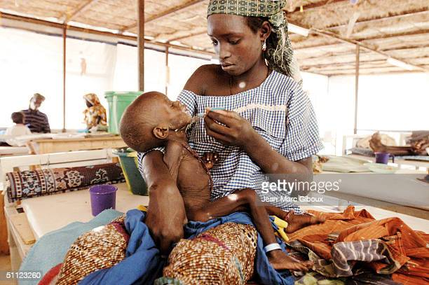 A mother feeds her malnourished child in the intensive care unit of the Medecinssansfrontieres clinic December 4 2003 in Maradi Niger Chronic...