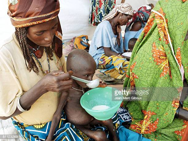 A mother feeds her severely malnourished child in nutrition center run by Medecinssansfrontieres clinic December 4 2003 in Maradi Niger Chronic...