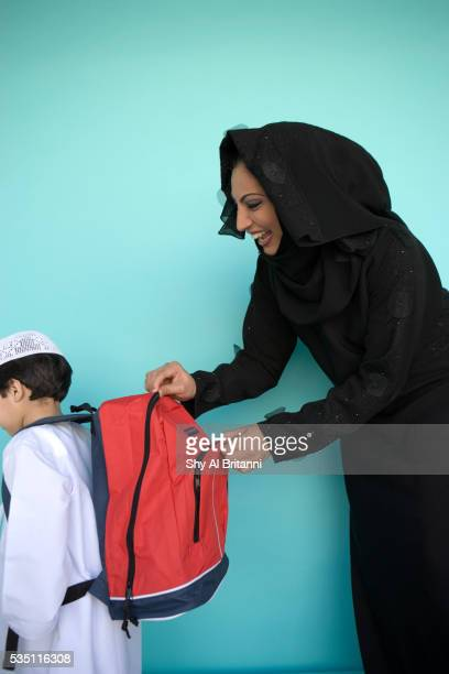 A mother fixes her son's school bag.