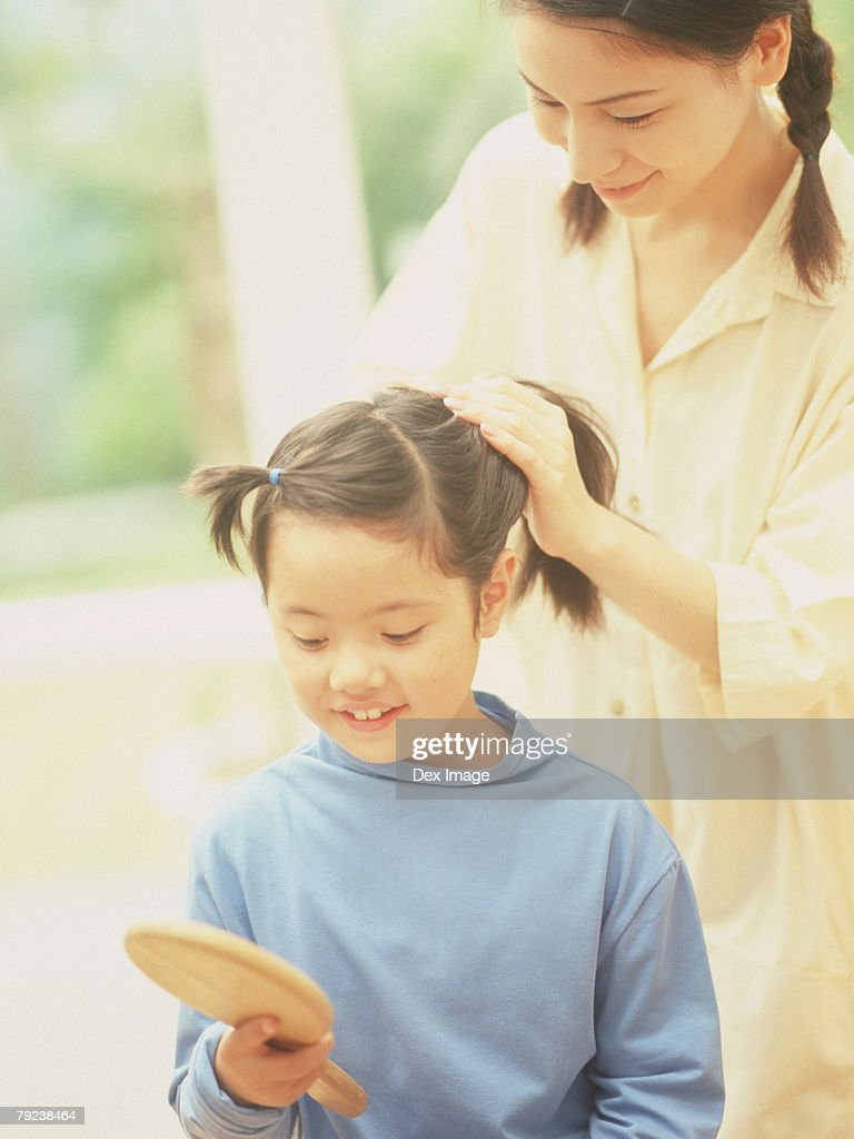 Mother fixing daughter's hair : Stock Photo