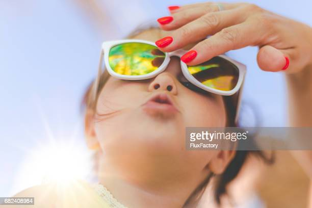 Mother fixing her daughter's sunglasses