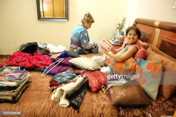 mother fixing messy room by putting the things on its proper place while daughter sitting on bed - punjab university stock pictures, royalty-free photos & images
