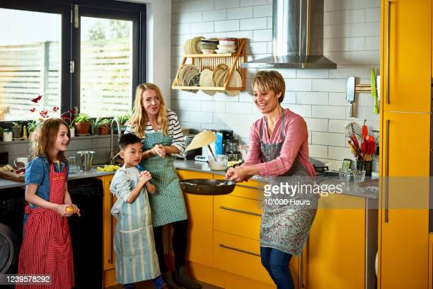 mother flipping pancake in kitchen with family - adoption stock pictures, royalty-free photos & images