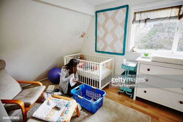 Mother folding laundry while baby lies in crib