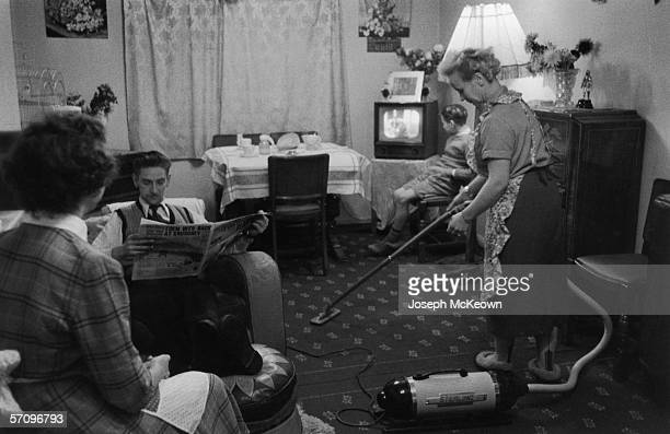A mother from Dagenham does the housework in the evening after a day's work 7th January 1956 Meanwhile her husband and two children sit reading or...
