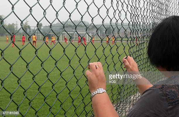A mother from Tianjin watches her child outside the field at Evergrande Football School on April 29 2015 in Qingyuan Guangdong Province of China...