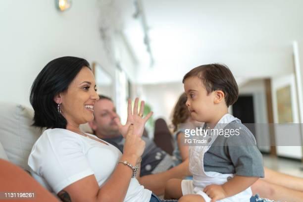 moeder gesturing/onderwijs met haar down syndroom zoon thuis - gebaren stockfoto's en -beelden