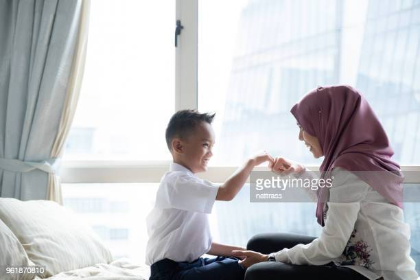 mother gets her son ready for school - malay stock photos and pictures