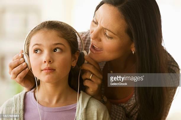 madre figlia di ottenere attenzione tirando indietro orecchio i telefoni fissi ed i cellulari - allerta foto e immagini stock
