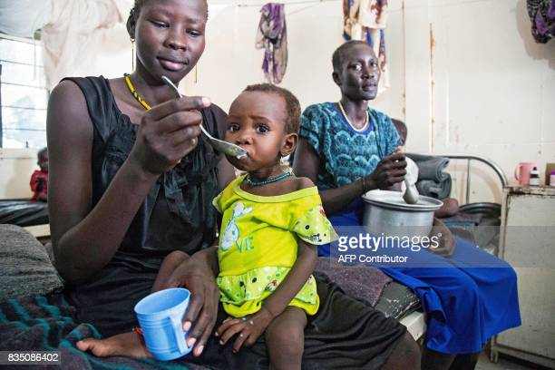 A mother gives food to her child with malnutrition in a clinic in Old Fangak Jonglei state on August 18 2017 The international community observes...