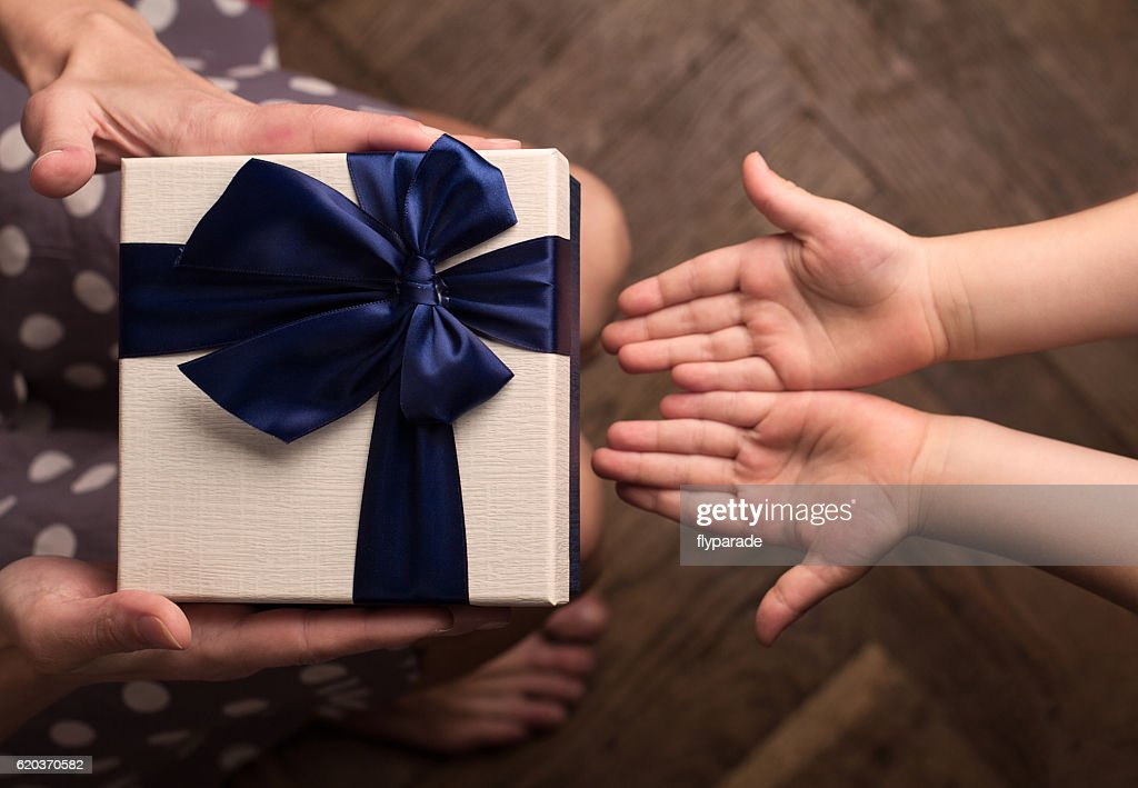 Mother giving a big gift boxes to her kid : Foto de stock
