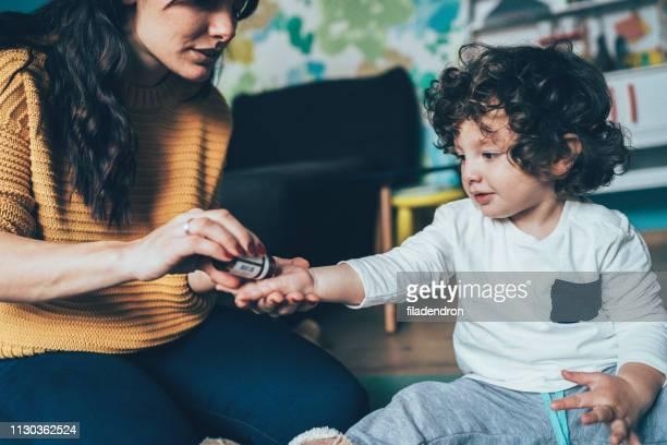 moeder geven een geneeskunde aan kind - vitamine stockfoto's en -beelden