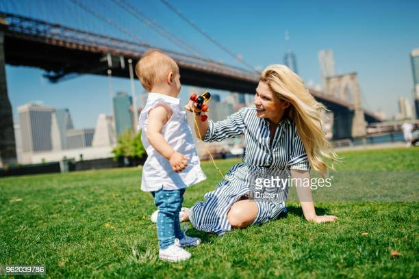 Mother giving a toy to her baby girl while playing in the park near the city