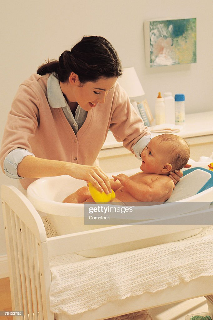 Mother giving baby a bath : Stockfoto
