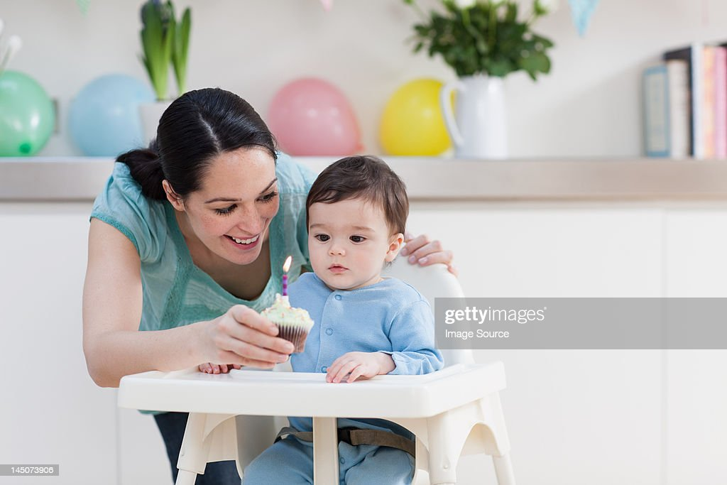 Mother Giving Birthday Cupcake To Baby Son In High Chair