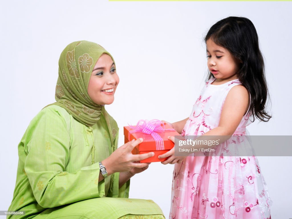 Mother Giving Birthday Gift To Daughter Against White Background Stock Foto