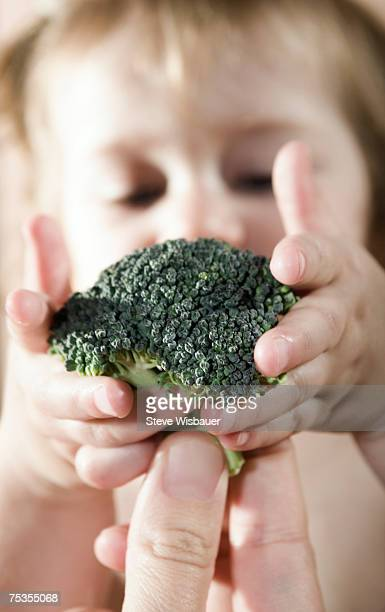 Mother giving broccoli to baby daughter (21-24 months)