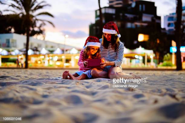 mother giving christmas present to her daughter on the beach - beach christmas stock pictures, royalty-free photos & images