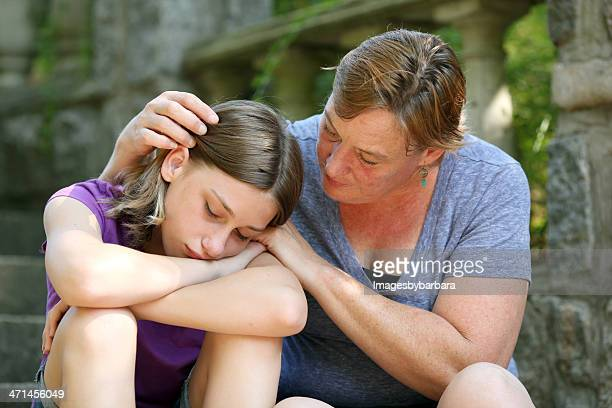 Mother giving comfort to teenage daughter.