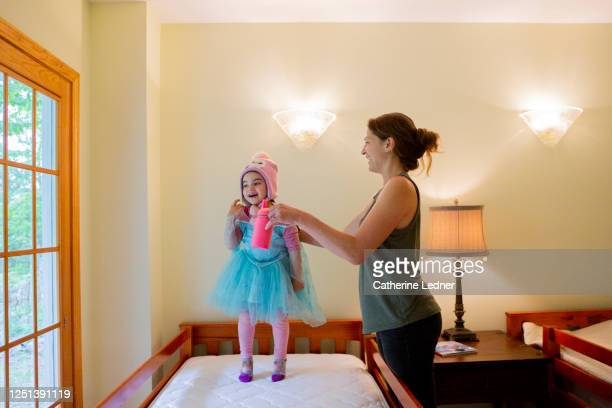 mother giving daughter a drink of water.  daughter has been jumping on the bed in her favorite costume - catherine ledner stock pictures, royalty-free photos & images