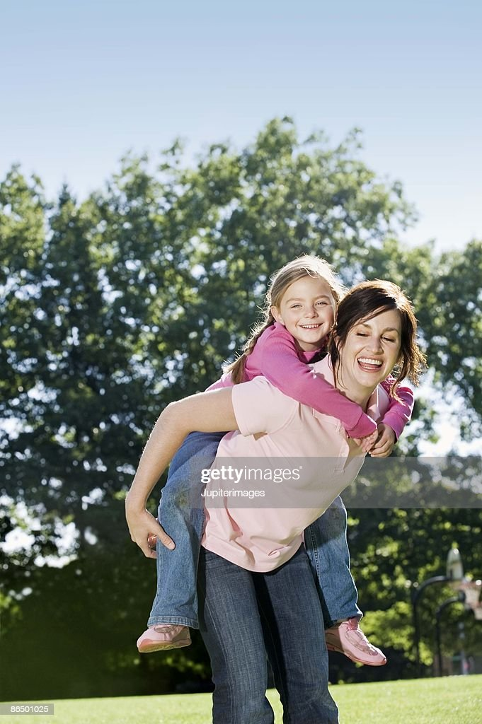 Mother giving daughter a piggy back ride : Stock Photo