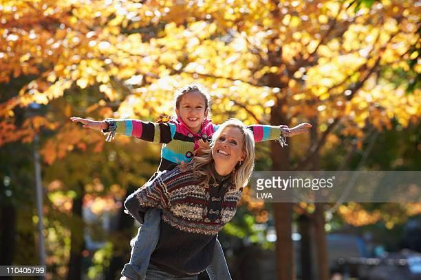 mother giving daughter a piggyback ride, outdoors - portare a cavalluccio foto e immagini stock