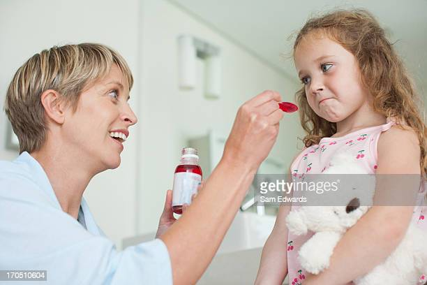 Mother giving daughter medicine