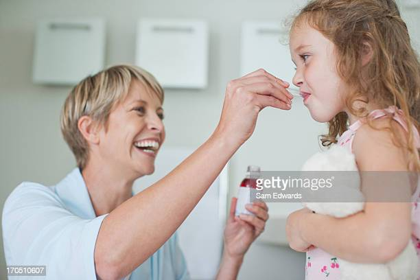 mother giving daughter medicine - taking a pill stock pictures, royalty-free photos & images