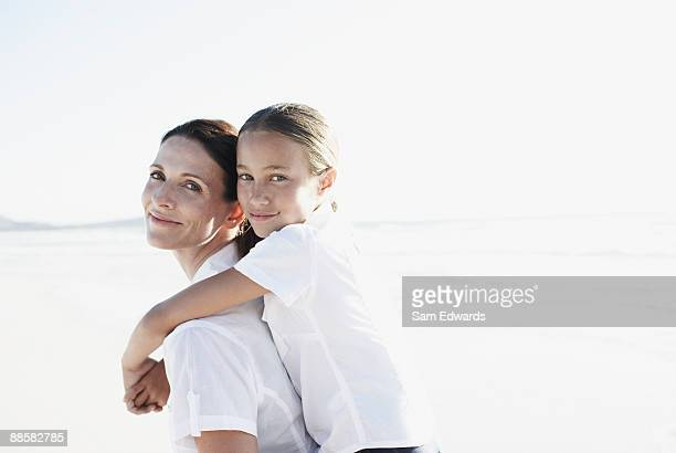 Mother giving daughter piggyback ride at beach