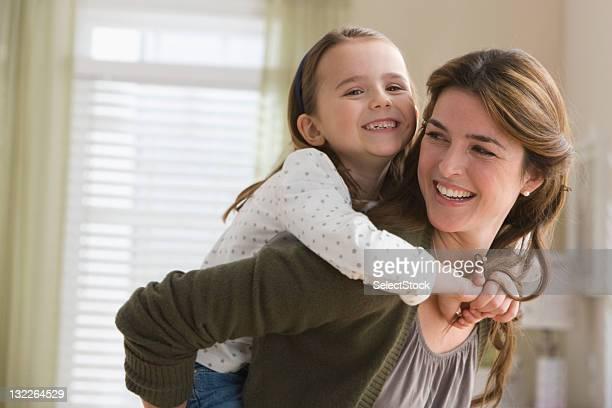 mother giving daughter piggyback ride - 35 39 jaar stockfoto's en -beelden