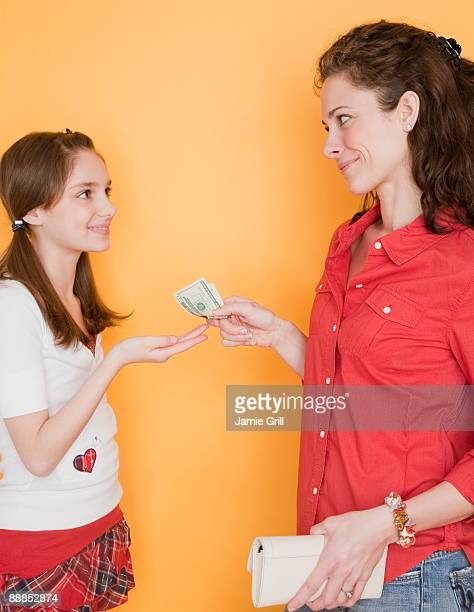 mother giving daughter (10-11 years) pocket money - family dollar stock pictures, royalty-free photos & images