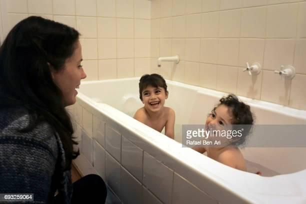 mother giving daughters bath - rafael ben ari fotografías e imágenes de stock