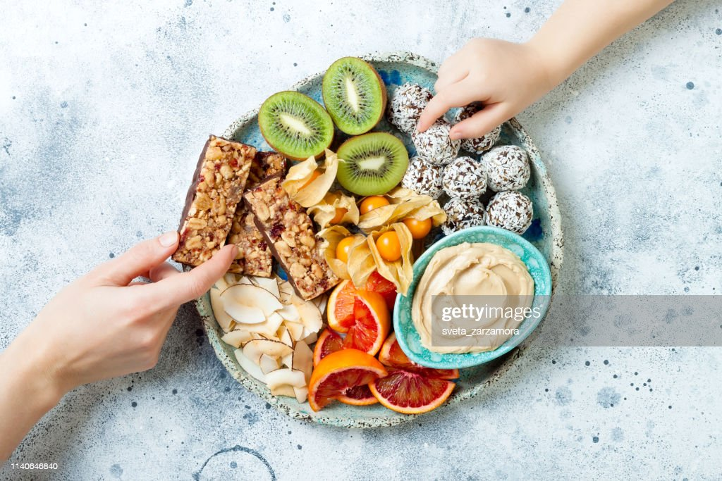Mother giving healthy vegan dessert snacks to toddler child. Concept of healthy sweets for children. Protein granola bars, homemade raw energy balls, cashew butter, toasted coconut chips, fruits platter : Stock Photo