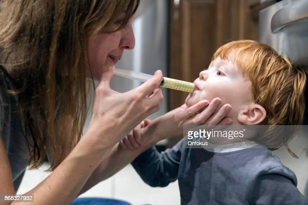 Mother Giving Penicillin Medicine to His Sick baby Boy