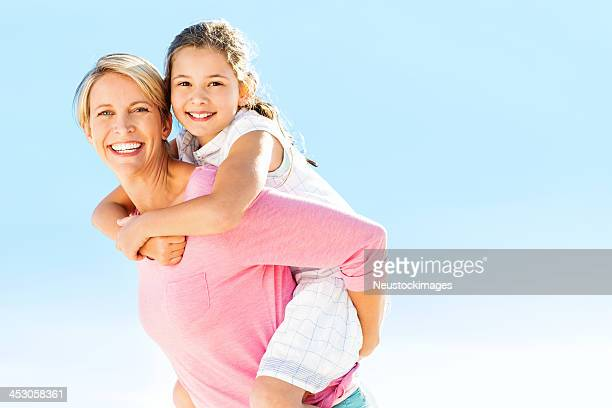 Mother Giving Piggyback Ride To Daughter Against Clear Blue Sky