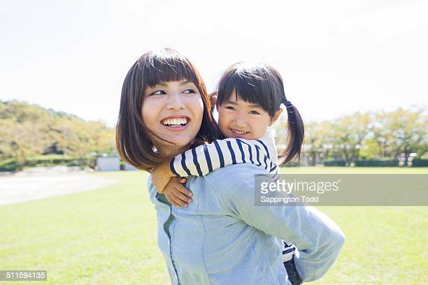 Mother Giving Piggyback Ride To Her Daughter