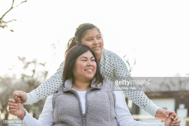 mother giving piggyback ride to her preteen daughter on beautiful day - mexican picnic stock pictures, royalty-free photos & images