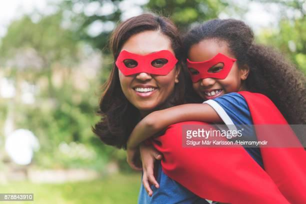 Madre dando piggyback a hija en traje de