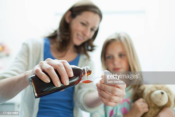 Mother giving sick daughter medicine