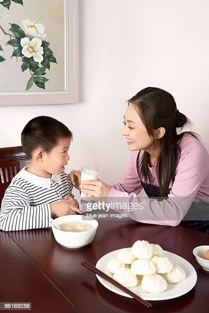 Mother Giving Son Glass Of Milk