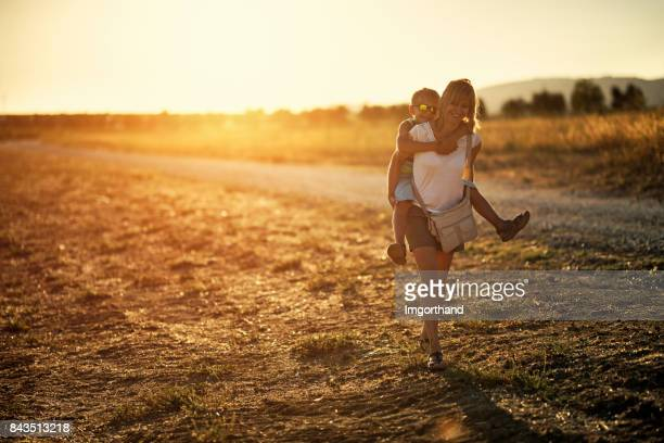 mother giving son piggyback ride on empty tuscan dirt road - hot mom stock photos and pictures