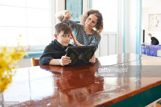 mother giving son with digital tablet haircut at dining table - 40 44 years stock pictures, royalty-free photos & images