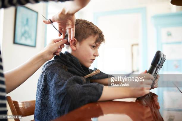 mother giving son with digital tablet haircut at dining table - gifted movie stock pictures, royalty-free photos & images