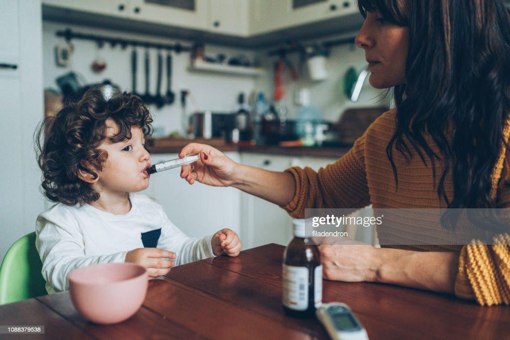 Mutter ihres Sohnes Sirup verleiht : Stock-Foto