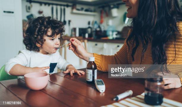 mother giving syrup to her son - syrup stock pictures, royalty-free photos & images
