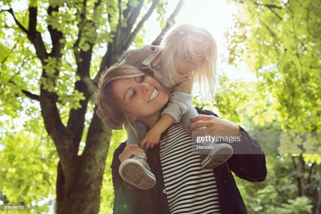 Mother giving toddler daughter shoulder carry in sunlit park : Stock-Foto