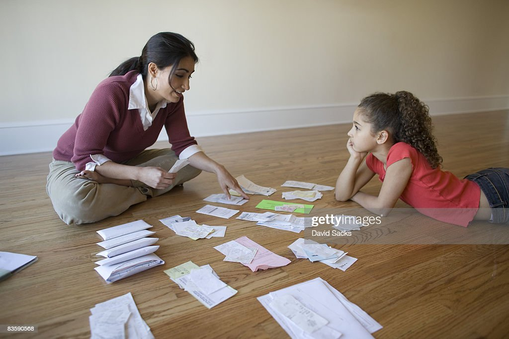 Mother going through bills with daughter : Stock Photo