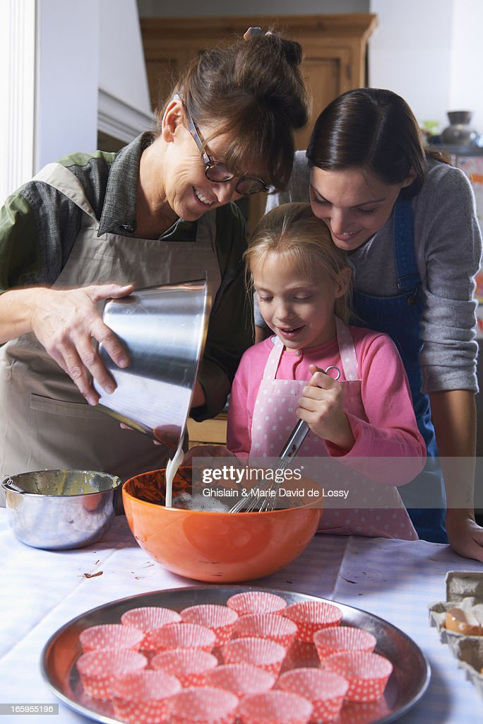 Mother, grand mother, and daughter baking a cake : Stock Photo